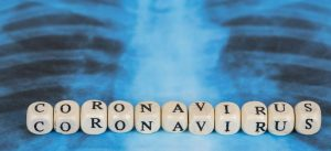 Novel Covid-19, Wuhan virus concept from China. Text phrase Coronavirus with wooden letter on lungs radiology blue image background. Copy space. Panoramic banner size