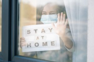 Concept of coronavirus quarantine. Child wearing medical protective face mask during flu virus, looking out of window. COVID-19. Teen girl holds board sign with text Stay at home. View from street.