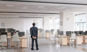 thoughtful businessman stands in front of empty office