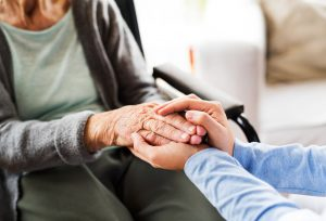 image of employee caring for older relative - holding hands